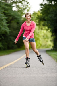 Smiling young woman in-line skating on paved path